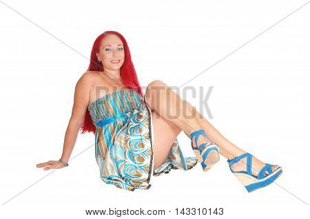 A woman in a dress and heels with long red hair sitting on the floor smiling isolated for white background.