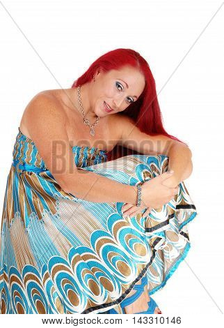 A beautiful woman in a colorful dress and long red hair sitting on a chair smiling isolated for white background.