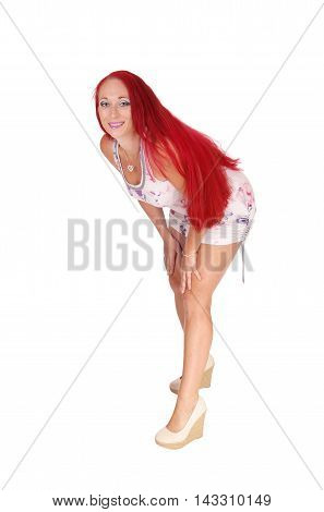 A woman with long red hear wearing a dress and heels bending forwards isolated for white background.