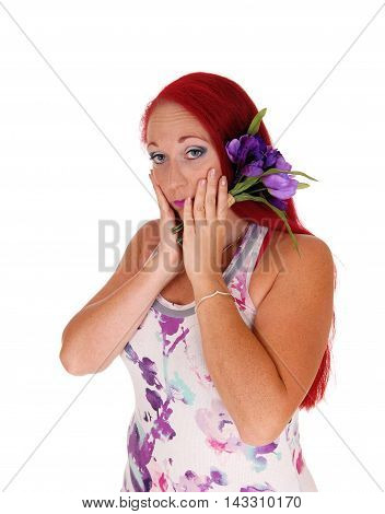 A woman with red hair holding her hands on her face and holding some purple flowers isolated for white background.