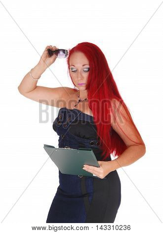 A business woman holding a clipboard to read on and glasses standing with long red hair isolated for white background.