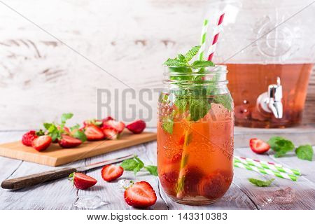 Homemade delicious strawberry compote in glass jar on white wooden table. Healthy food concept with copy space.