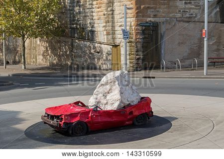 SYDNEY, AUSTRALIA - APRIL, 2016 : Huge stone dropped on red car called Still Life with Stone and Car, by American artist display at Pottinger roundabout in Sydney, Australia on April 20, 2016