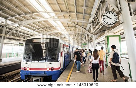 People at a railway station traveling by train Bangkok Thailand (Focus on clock)