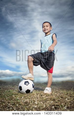 Feet of child on football / soccer ball on grass. Child playing football