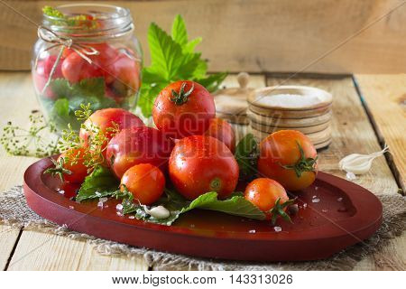 Preserving Fresh And Pickled Tomatoes, Spices And Garlic On A Wooden Table. Home Canned Vegetables.