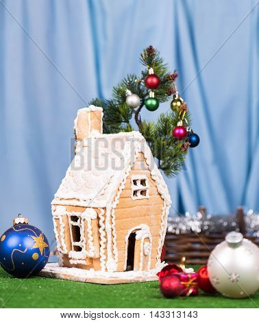 Gingerbread lodge with Christmas gifts and toys over blue background