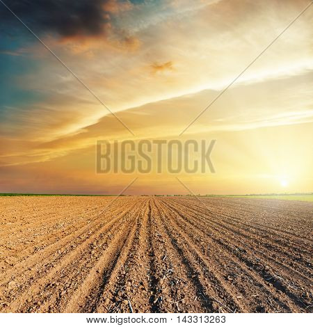 dramatic orange sunset and plowed field