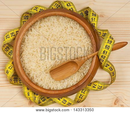 Raw rice in a bamboo bowl with tape measure over wooden surface