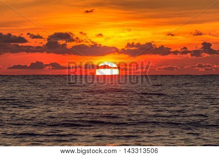 Vintage style image of the sunset sky over the calm surface of the sea.