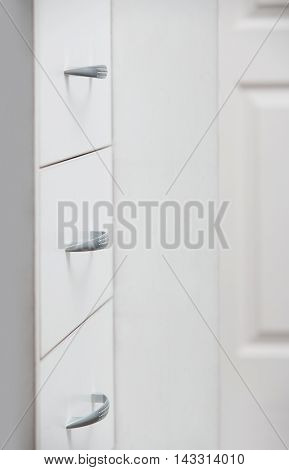 Cabinet with sliding trays and chrome handles. Vertical photo
