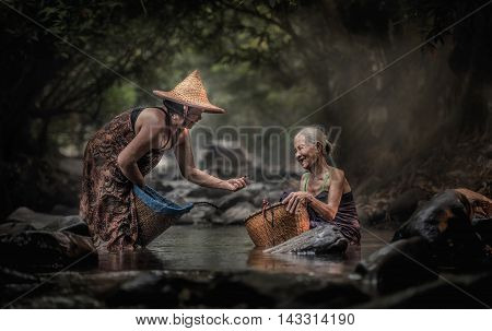 Old Asian woman working in cascade Thailand