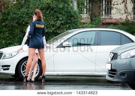 Young beautiful police woman stops car for checking driver license