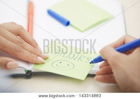 Hands of woman writing Thanks text on a sticky note