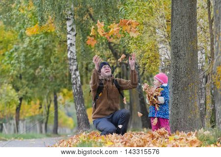 Father with raised hands is tossing up yellow fallen leaves with his daughter in colorful autumn park outdoors