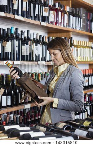 Female Customer Removing Wine Bottle From Bag