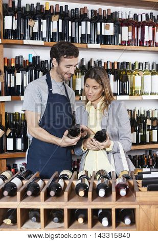 Salesman And Customer Discussing Over Wine Bottles