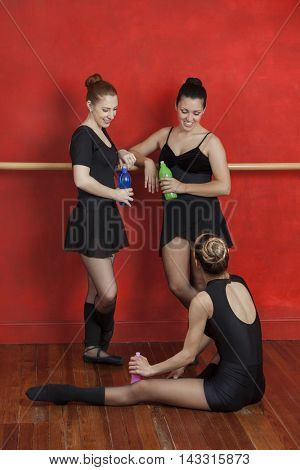 Happy Ballerinas With Water Bottles In Dance Studio