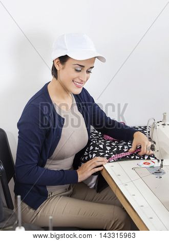 Smiling Tailor Measuring Fabric At Workbench