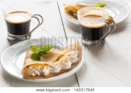 A light breakfast or lunch for two, with pancakes (crepes) and whipped cream. On the table is the coffee. Sunny morning, white wooden table, top view