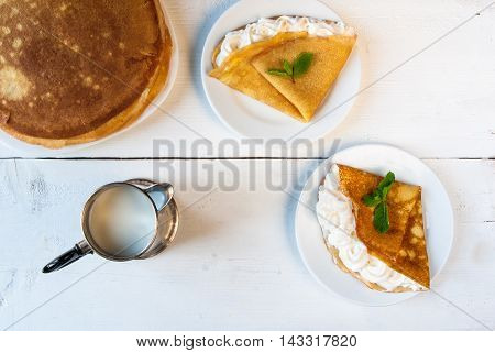 A light breakfast or lunch for two, with pancakes (crepes) and whipped cream. On the table is the milk. Sunny morning, white wooden table, top view