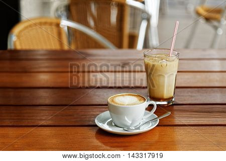 A Cup Of Cappuccino And A Glass Of Iced-latte
