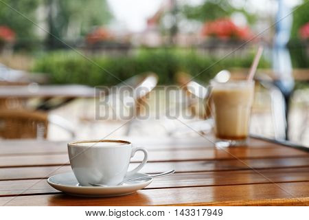 Cup Of Cappuccino On Wooden Table In A Street Coffee Shop