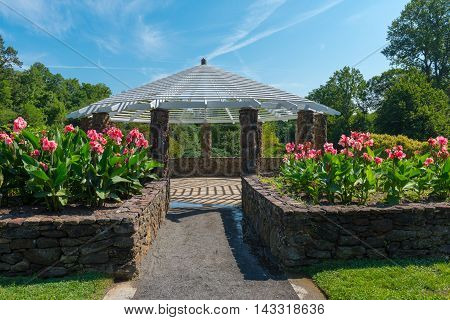 Gazebo surrounded by flowers and trees in a park under a blue sky