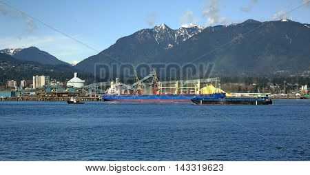 Terminal of North Vancouver port on a background of mountain scenery. The vessel is under load, the tug is towing another vessel.