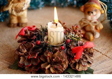 Wax candle on a decorative support from cones