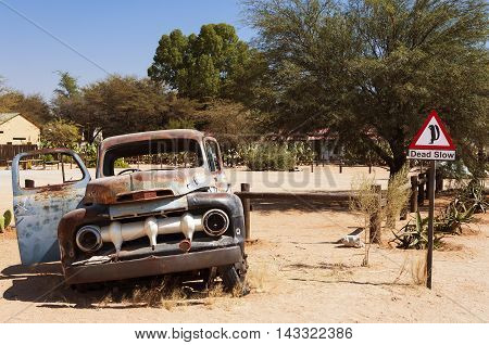Old rusty car and road sign in Solitaire Namibia