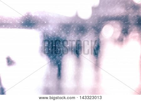 Winter city commuters with snow. Blurred image of people walking on the street. Defocused figures of people with snowing effect and frost.