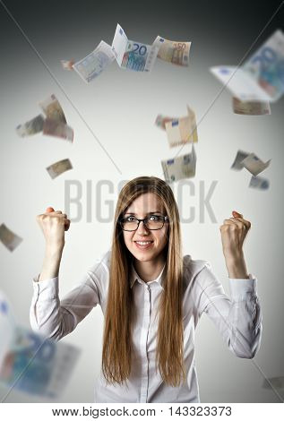Rejoicing. Woman in white and falling Euro banknotes. Success currency and lottery concept.