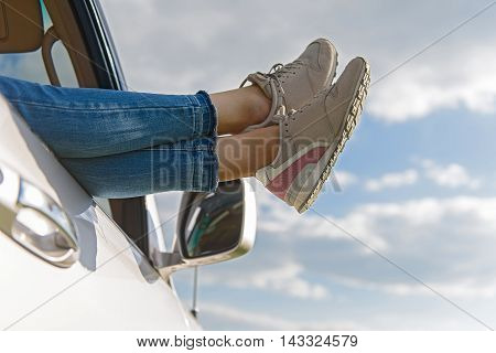 Time to relax. Close up of woman legs out window in car above clouds
