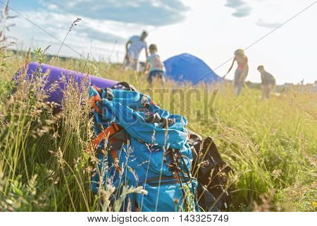 Family camping is family bonding. Close up of backpack lying on grass with family putting up tent together in background