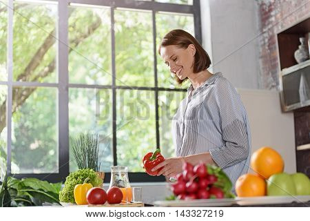 Cheerful young woman is cooking in kitchen. She is holding pepper and smiling. Lady is standing near fresh fruits and vegetables