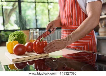 Close up of young man hands cutting vegetable with knife. He is standing near table in kitchen
