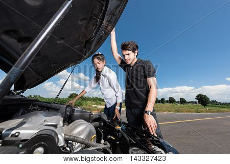 Man and woman stand by the broken car and don't know what to do