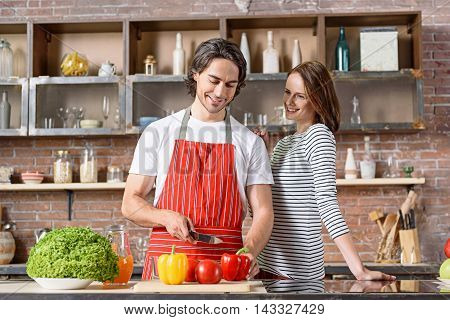 Happy married couple is cooking breakfast at home. Man is cutting vegetables and smiling. Woman is looking at him with curiosity