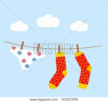 underwear and socks drying on the clothesline against a beautiful blue sky backdrop