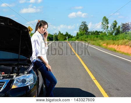 Young girl with broken down car with hood open call for help
