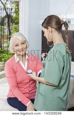 Senior Patient Getting Her Blood Pressure Checked By Female Nurs