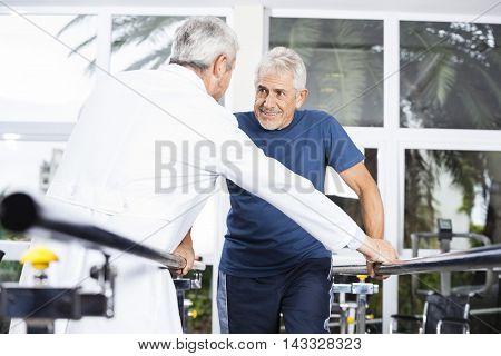Senior Man Looking At Doctor While Walking In Fitness Studio