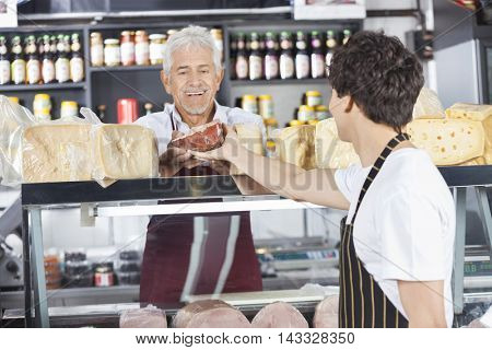 Happy Salesman Receiving Cheese From Colleague In Grocery Shop