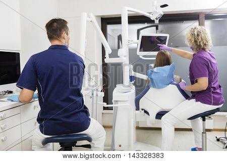 Dentist Looking At Colleague Pointing At Screen While Examining