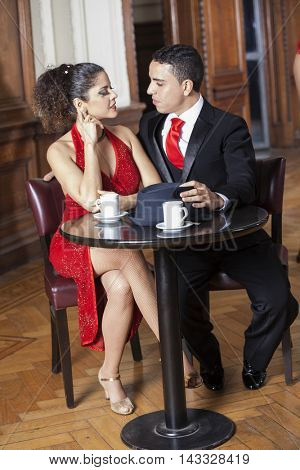 Tango Couple Sitting At Table In Restaurant