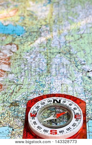 Travel and adventure! The magnetic compass lies on a topographic map.