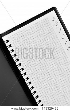 Checked spiral phone book, address notebook background pattern, vertical chequered squared open notepad, isolated retro copy space, stapled blank empty alphabet blocknote, contact reminder concept metaphor, large detailed macro closeup