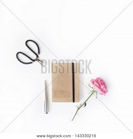 pink rose scissors craft diary and pen on white background. flat lay top view