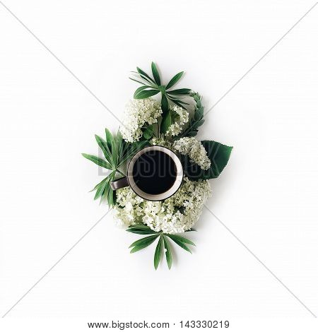 black coffee mug and white hydrangea flowers bouquet on white background. flat lay top view